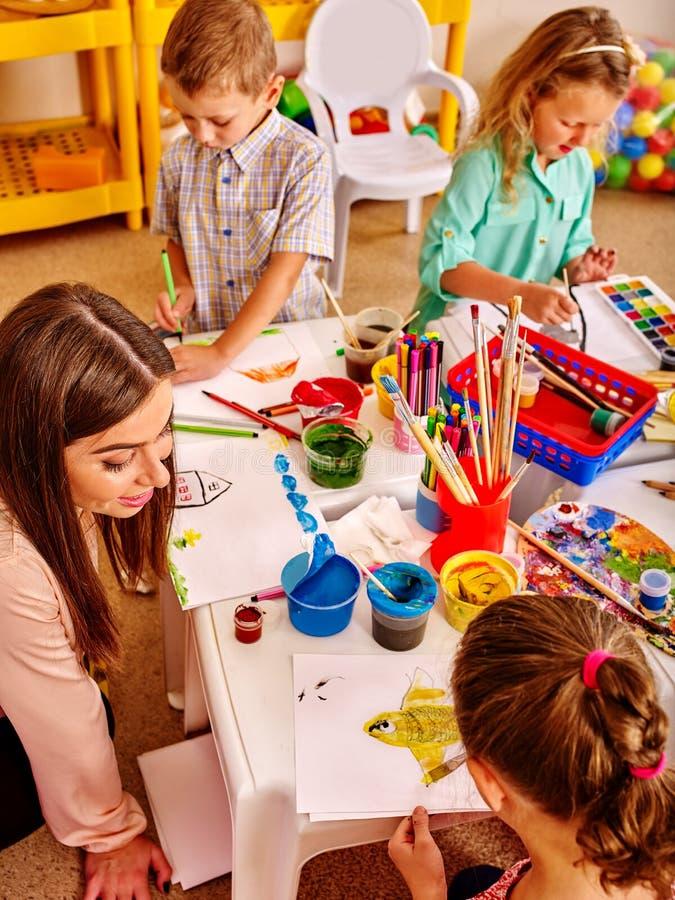 Barn med lärarekvinnamålning på papper i dagis royaltyfri fotografi