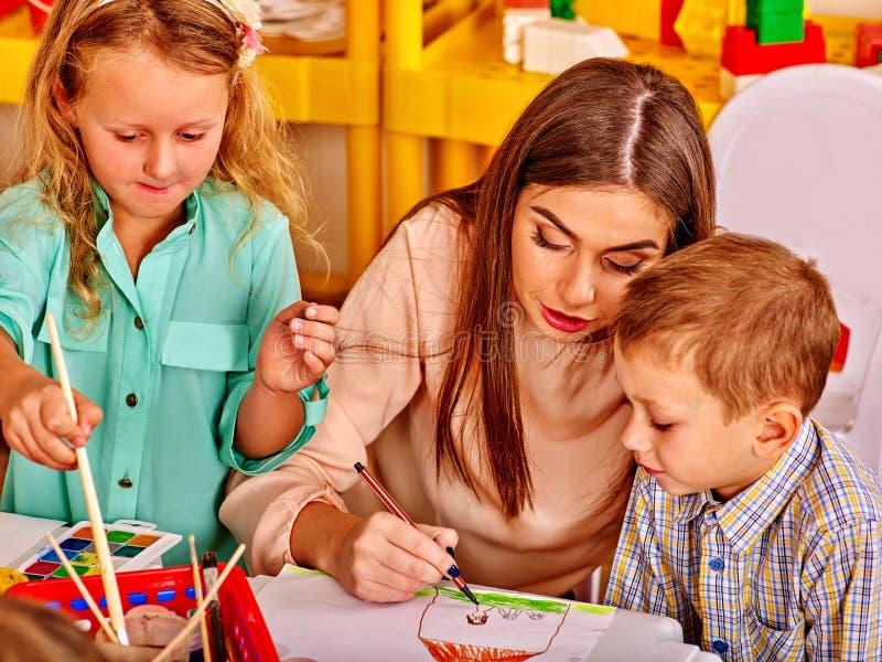 Barn med lärarekvinnamålning på teckningskurs arkivfoto