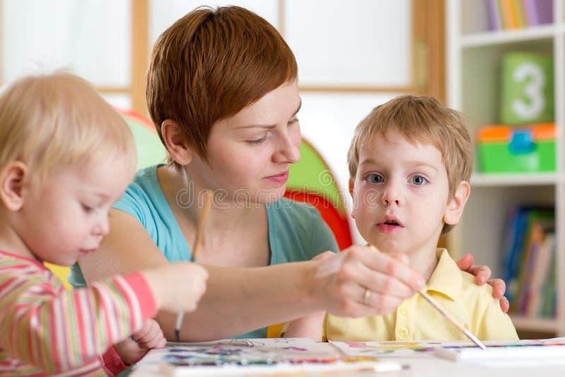 Barn med läraremålning i playschool arkivfoto