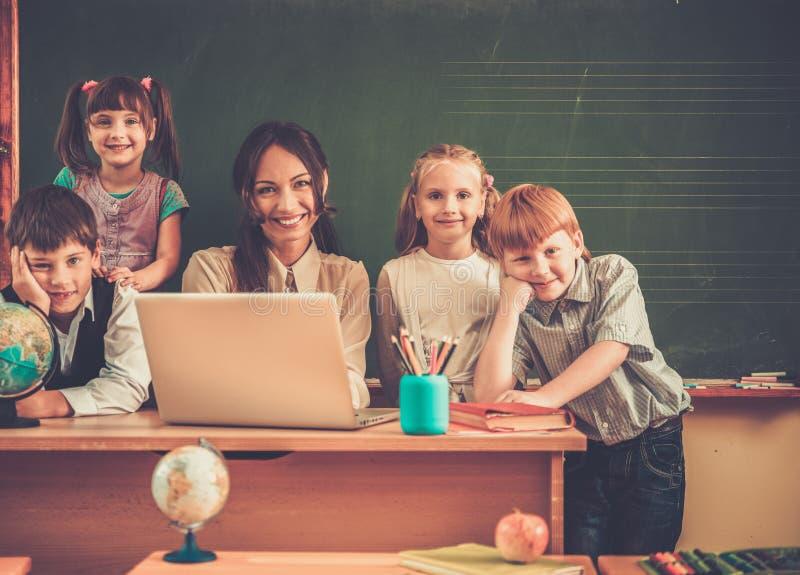 Barn med läraren under kurs i skola arkivfoto