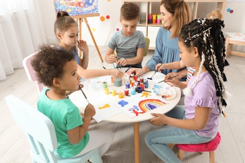 Barn med l?rarinnan p? m?lningkursen royaltyfria bilder