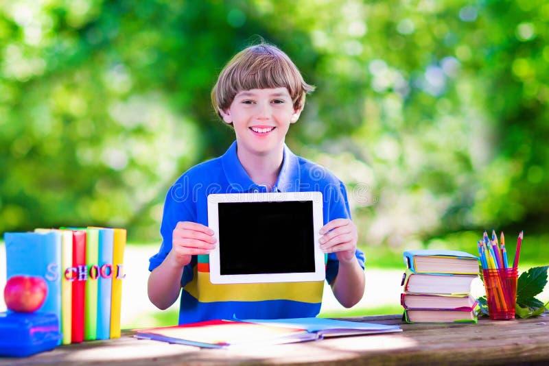 Barn med minnestavladatoren på skolgård royaltyfria foton