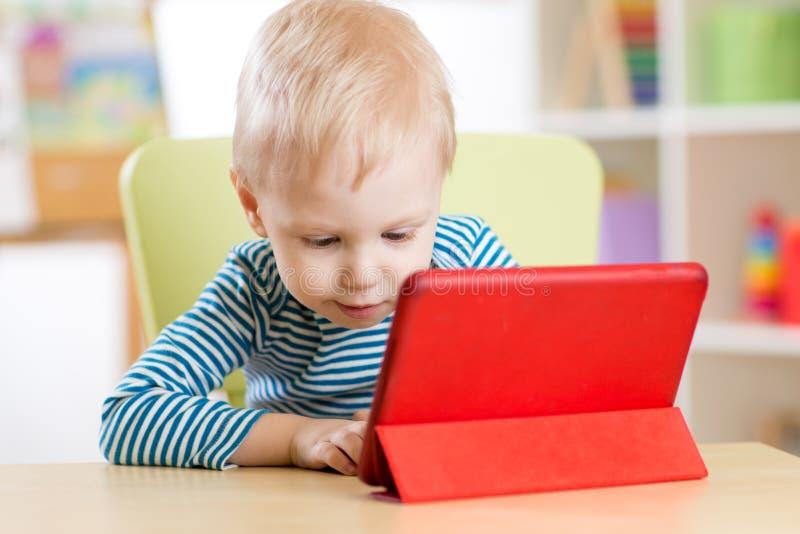 Barn med minnestavlaPCdatoren hemma royaltyfria foton