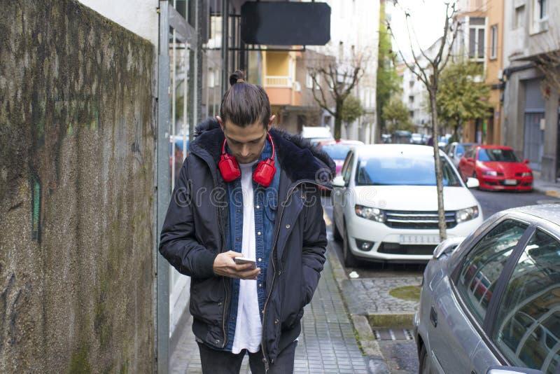 Barn med mobiltelefonen på gatan royaltyfri foto