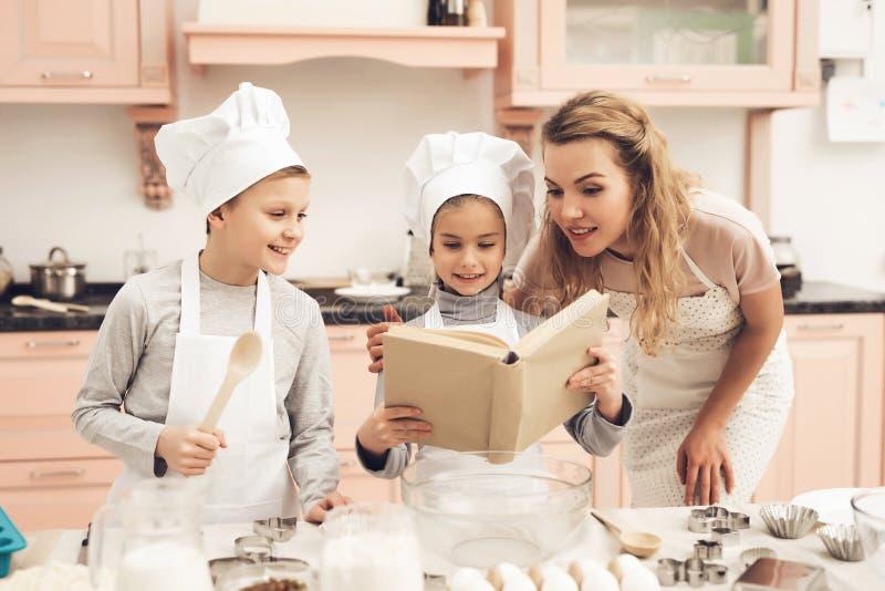 Barn med modern i kök Familjen är det läs- receptet i kokbok arkivfoton