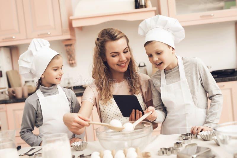 Barn med modern i kök Familjen är det läs- receptet på minnestavlan arkivbilder