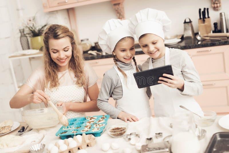 Barn med modern i kök Modern sätter deg i bakningmaträtt, och ungar ser på minnestavlan arkivbilder
