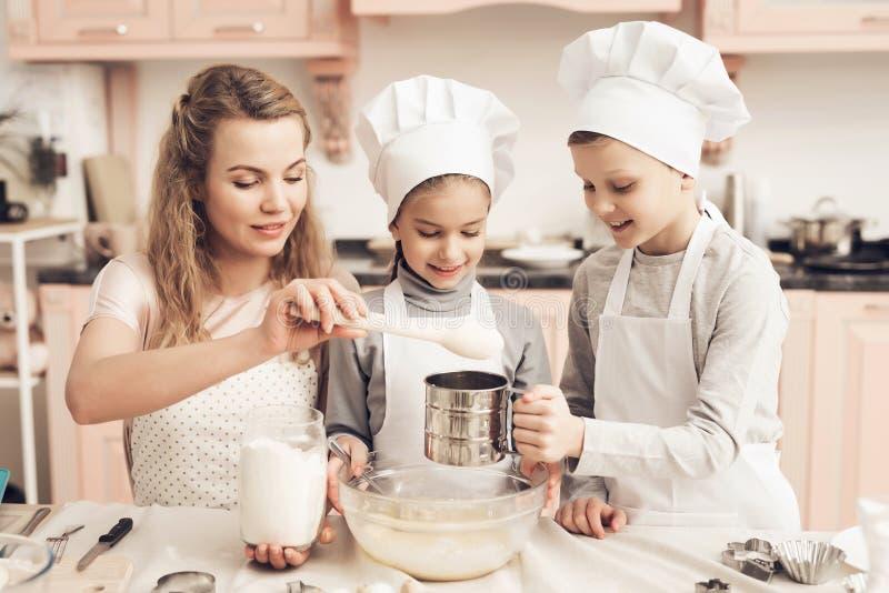 Barn med modern i kök Modern tillfogar mjöl, broder siktar det royaltyfri fotografi