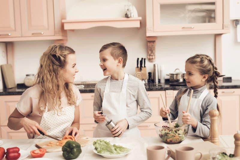 Barn med modern i kök Ungar hjälper modern att göra sallad fotografering för bildbyråer