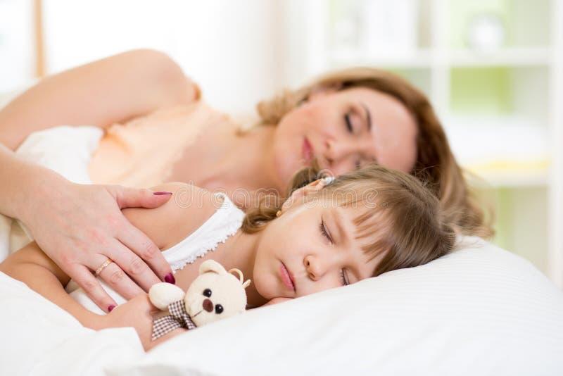 Barn med modern som förbereder sig för att ta sig en tupplur på säng arkivfoton