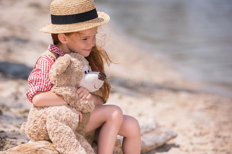Barn med nallebjörnen på kusten arkivbilder