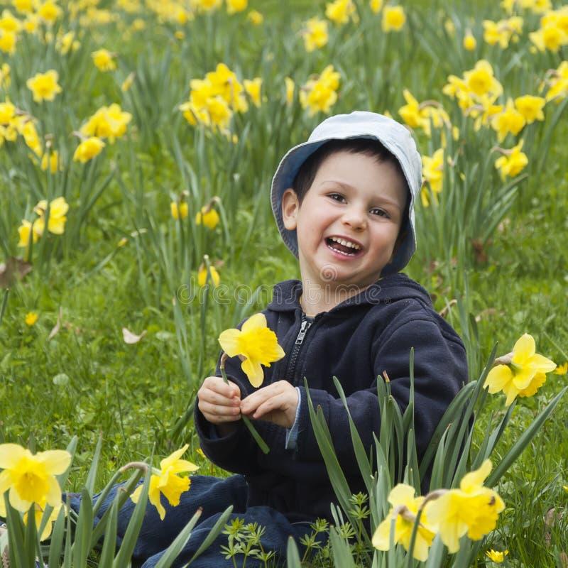 Barn med påskliljar arkivbild