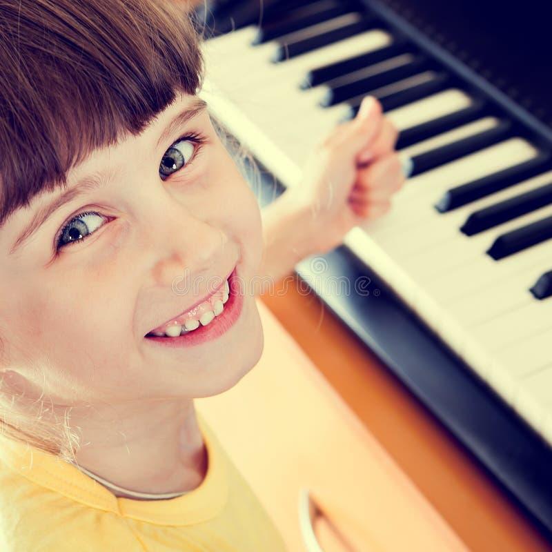Barn med pianot royaltyfria foton