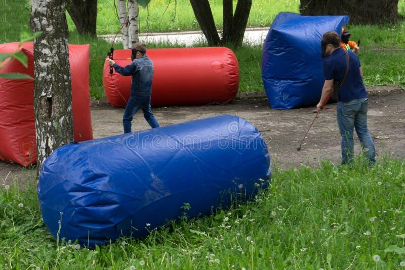 Barn med pilbågar som spelar paintball arkivbild