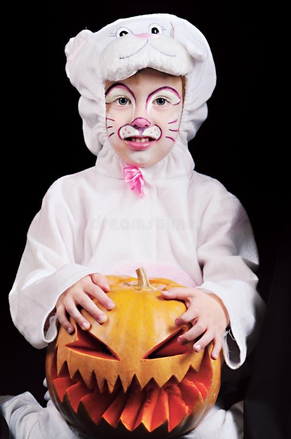 Barn med pumpa i kaninmaskeradkläder arkivbilder