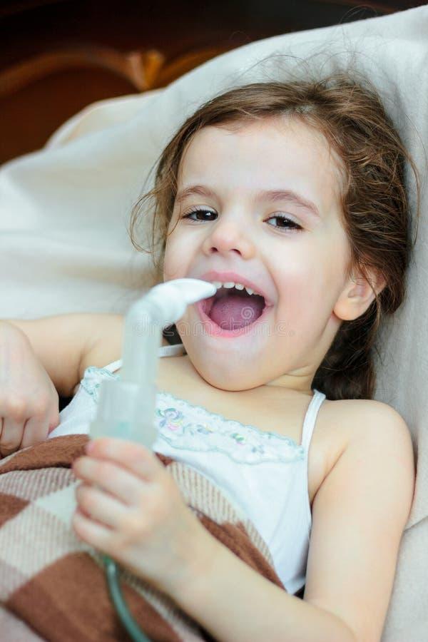 Barn med respiratorisk sjukdomdanandeinandning med inhalatorn royaltyfria foton