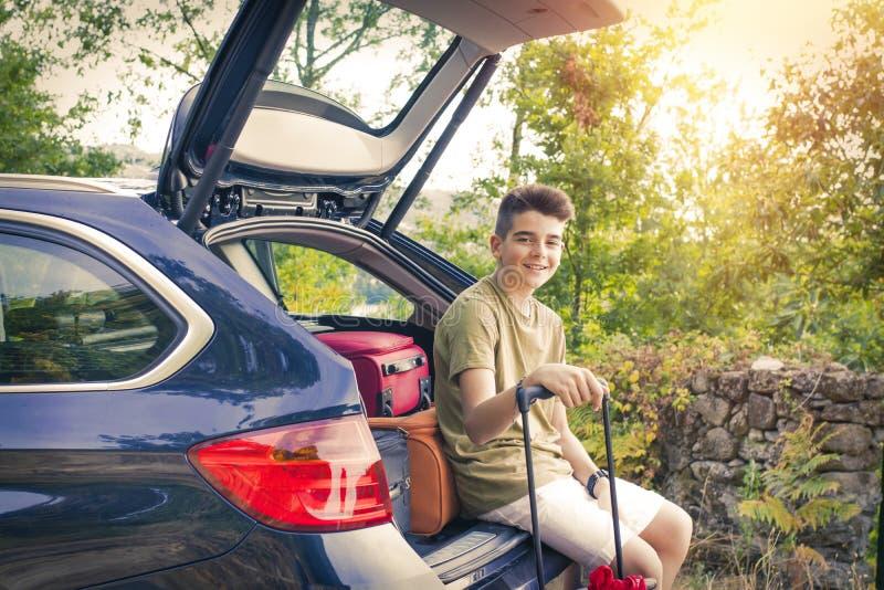 Barn med resväskor och bilen arkivfoto