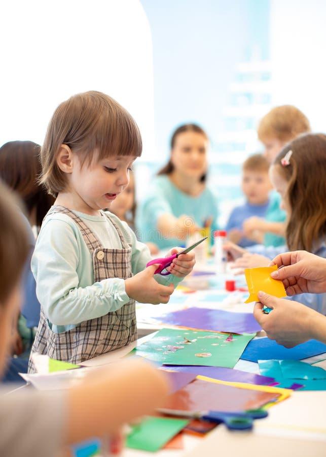 Barn med sax i händer som klipper papper med läraren i grupprum Grupp av barn som g?r projekt i dagis royaltyfri fotografi