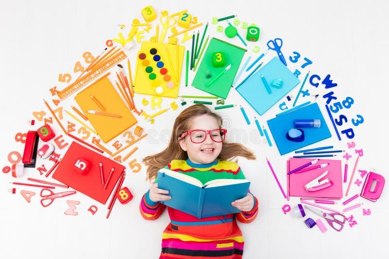 Barn med skola- och teckningstillförsel Deltagaren med bokar arkivbild