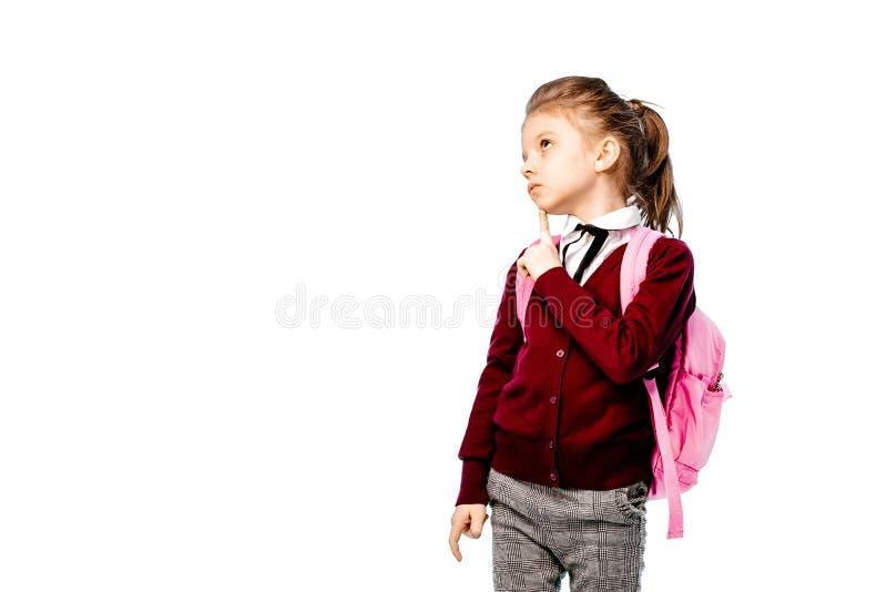 Barn med skolväskan Flickan i den vita skjortan och gråa flåsanden, rymmer en skolapåse och att posera som modell Isolerat på vit royaltyfria foton