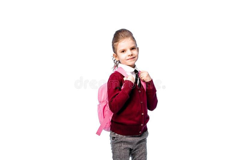 Barn med skolväskan Flickan i den vita skjortan och gråa flåsanden, rymmer en skolapåse och att posera som modell Isolerat på vit royaltyfri fotografi