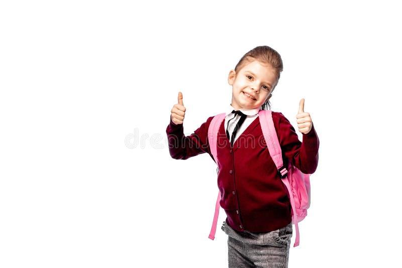 Barn med skolväskan Flickan i den vita skjortan och gråa flåsanden, rymmer en skolapåse och att posera som modell Isolerat på vit royaltyfri bild