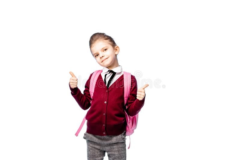 Barn med skolväskan Flickan i den vita skjortan och gråa flåsanden, rymmer en skolapåse och att posera som modell Isolerat på vit royaltyfria bilder