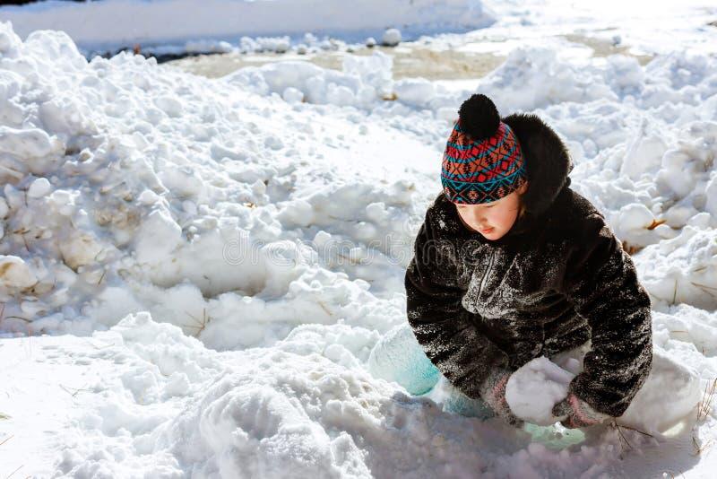 Barn med skyffeln som utomhus spelar i vintersäsong Lycklig liten flicka som spelar i ett snöig landskap arkivfoton