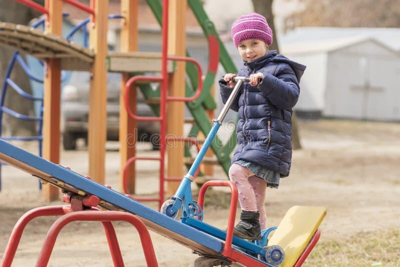 Barn med sparksparkcykeln på lekplatsen royaltyfri bild