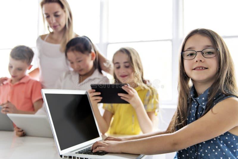 Barn med teknologiminnestavlan och bärbar datordatoren i klassrumlärare på bakgrunden royaltyfria bilder