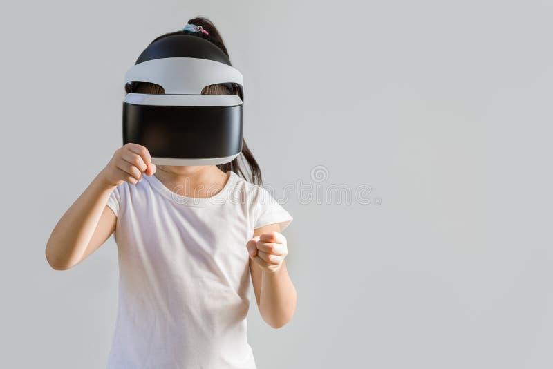 Barn med virtuell verklighet, VR, hörlurar med mikrofonstudioskott som isoleras på vit bakgrund Unge som undersöker Digital den f arkivfoto