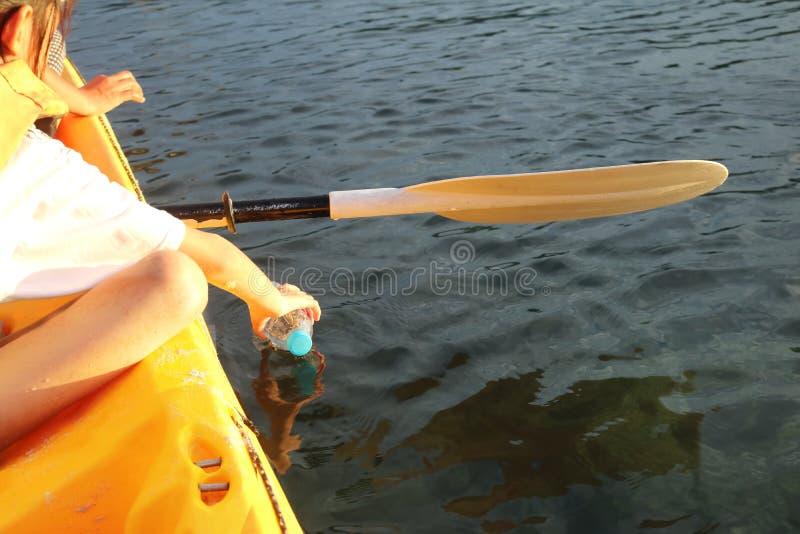 Barn når för en flaska av plast-avfalls i havet royaltyfri fotografi