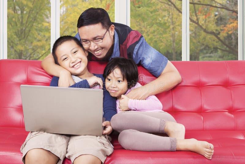 Barn och deras farsa som hemma använder bärbara datorn royaltyfri foto