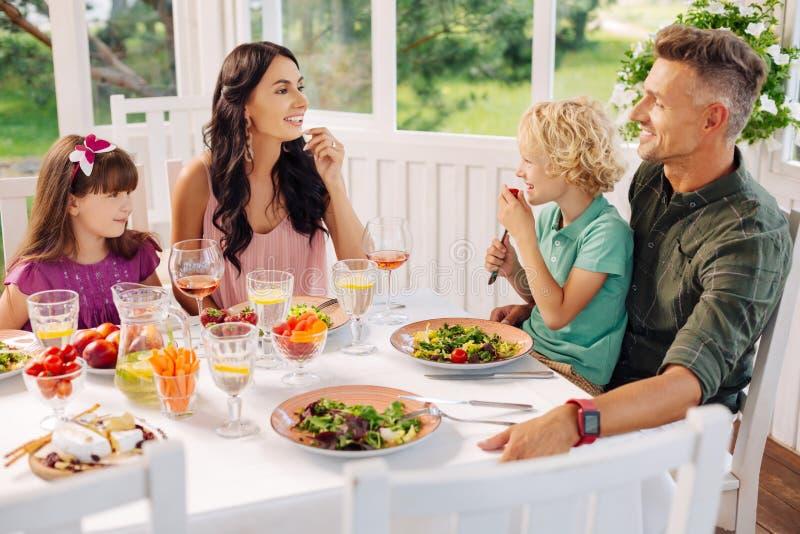 Barn och föräldrar som äter smaskiga sallader och samtal fotografering för bildbyråer