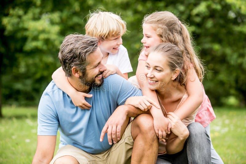 Barn och föräldrar som den lyckliga familjen arkivbild