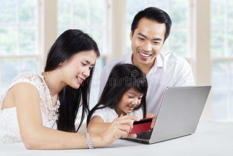 Barn och henne föräldrar som direktanslutet hemma shoppar arkivfoto