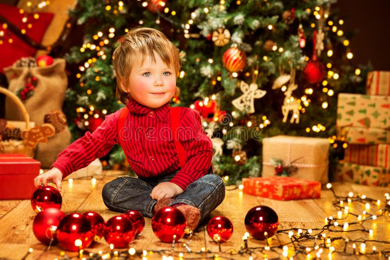 Barn och julgran, lycklig pojkeunge med bollar för nytt år för Xmas royaltyfri foto