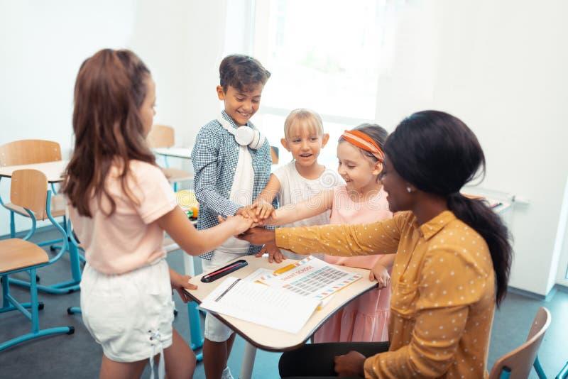 Barn och lärare tycka om deras allt lagarbete tillsammans royaltyfri bild