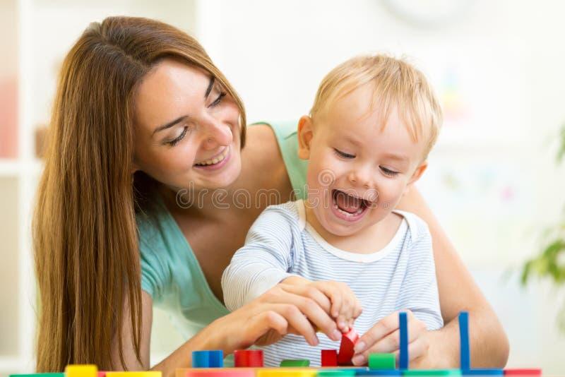 Barn och mamma som spelar samman med pusselleksaken royaltyfri foto