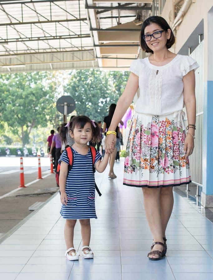 Barn och modern går till första dagbruk för skolan för utbildning, ki royaltyfri foto