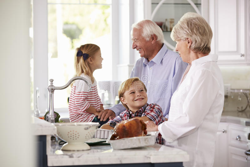 Barn och morföräldrar gör stekTurkiet mål i kök arkivbild
