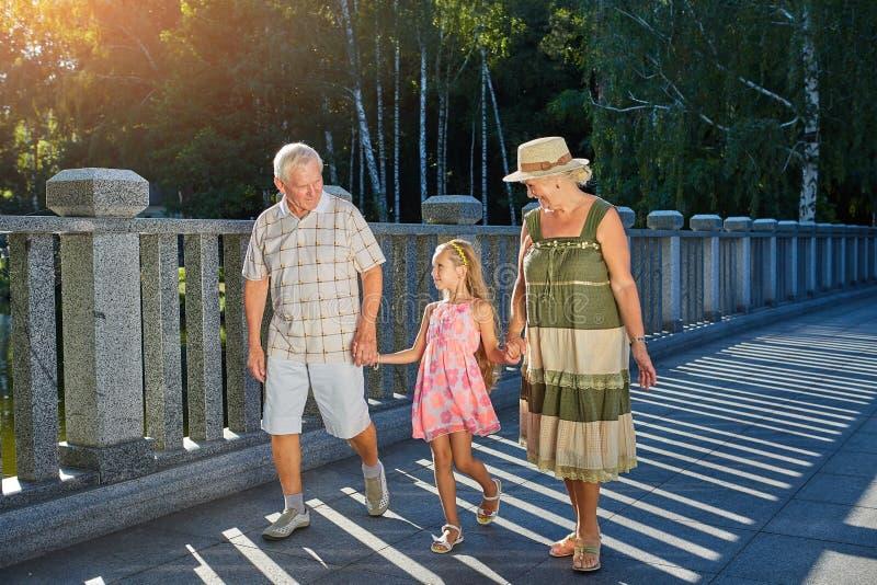 Barn och morföräldrar som rymmer händer royaltyfri bild
