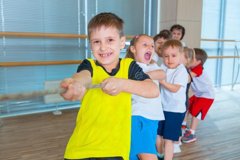 Barn och rekreation, grupp av den lyckliga multietniska skolan lurar att spela dragkampen med repet i idrottshall arkivbilder