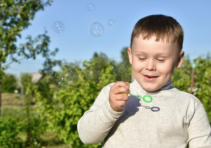 Barn och såpbubblor royaltyfria foton