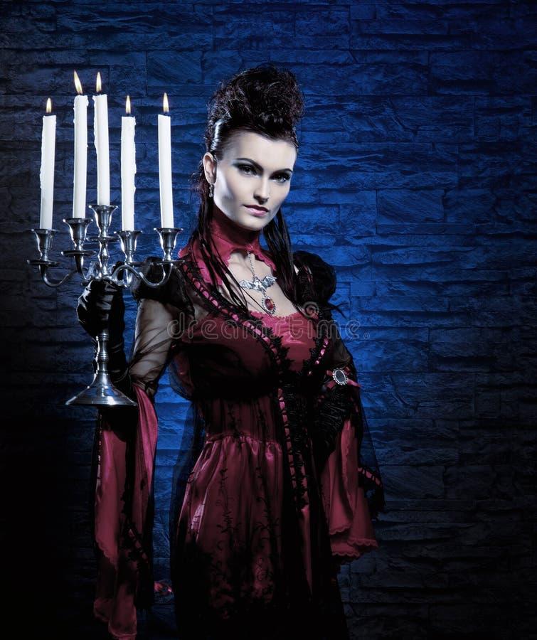 Barn och sexiga stearinljus för ladyvampyrholding royaltyfri foto