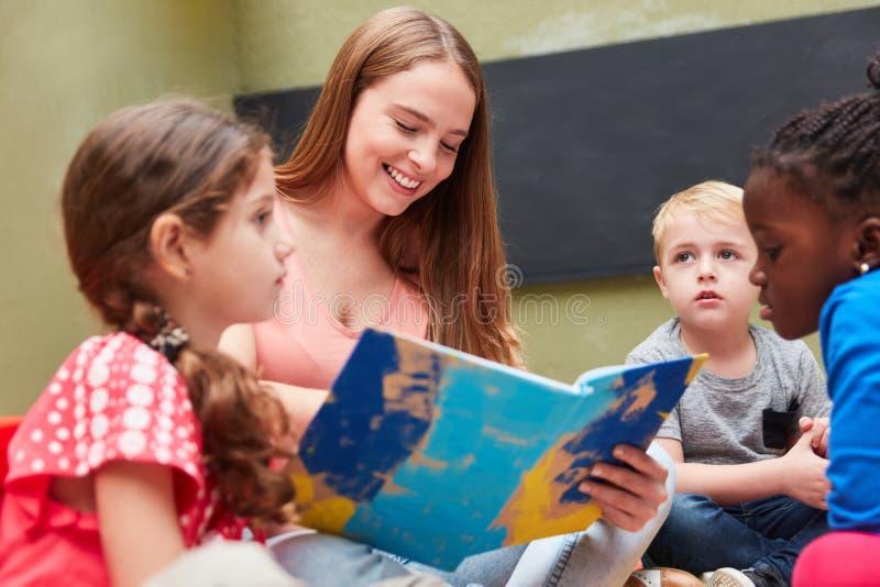 Barn och utbildare som aloud läser royaltyfria bilder