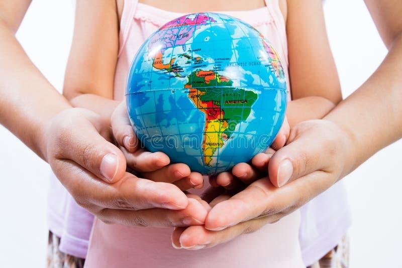 Barn och vuxen människa som rymmer ett världsjordklot i händer arkivfoton
