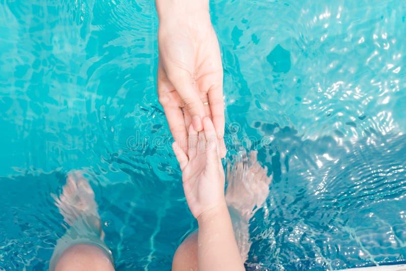 Barn- och vuxen människaben som är undervattens- i simbassängen royaltyfria bilder