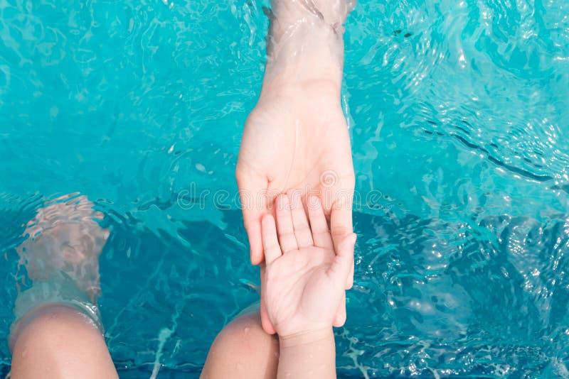 Barn- och vuxen människaben som är undervattens- i simbassängen royaltyfria foton