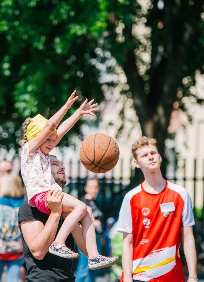 Barn och vuxna människor som spelar basket parkerar in, tillsammans royaltyfri foto